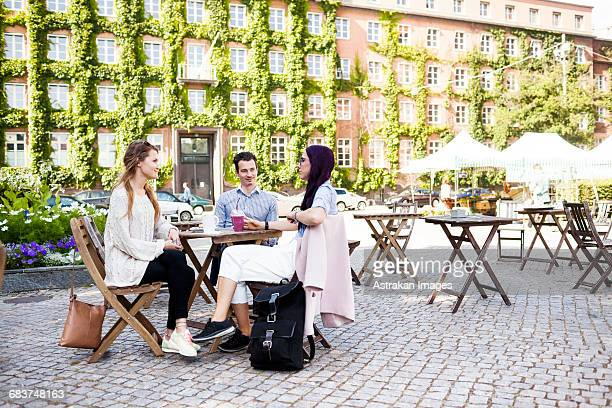 friends discussing at sidewalk cafe in town square - pavement cafe stock pictures, royalty-free photos & images