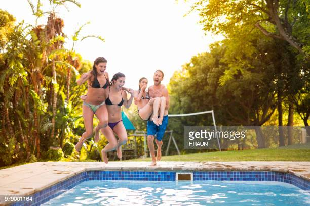 Friends diving in swimming pool at resort in garden party.