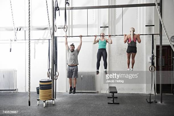 Friends doing chin-up in cross training gym