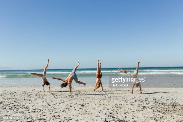 friends doing hand stands on  the beach - acrobatic activity stock photos and pictures
