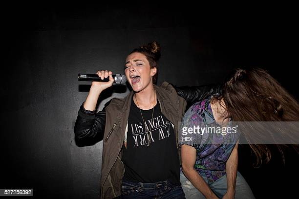 friends doing karaoke at a nightclub - cantare foto e immagini stock