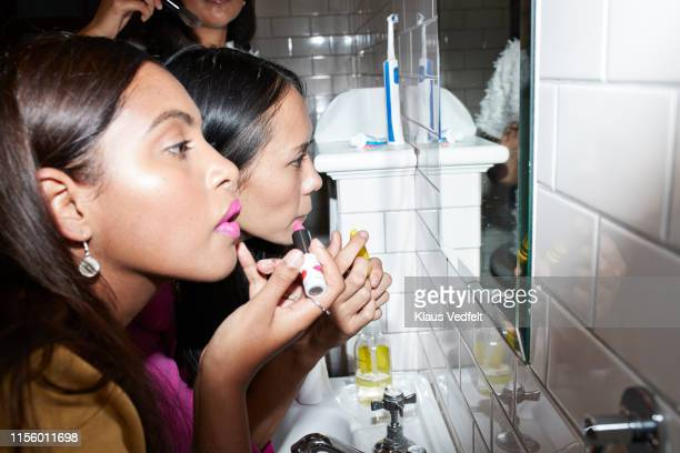 friends doing make-up together - pintalabios rosa fotografías e imágenes de stock