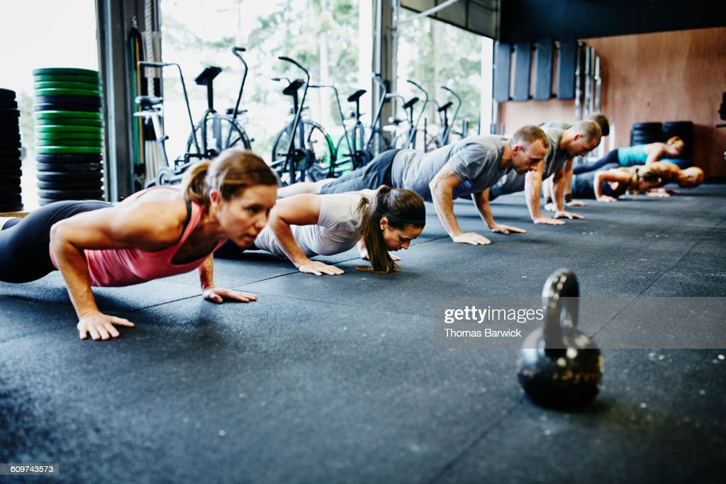 Friends doing pushups during workout in gym : Stock Photo