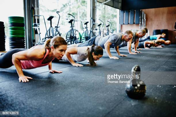 Friends doing pushups during workout in gym