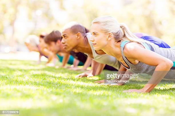 Friends Doing Push-Ups In Park