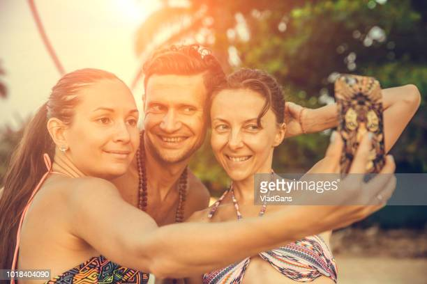Friends doing selfie photo on the beach