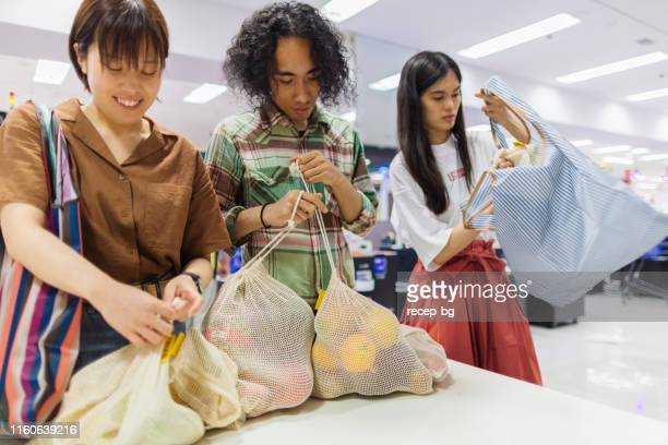 Friends doing shopping at supermarket with their reusable shopping bag