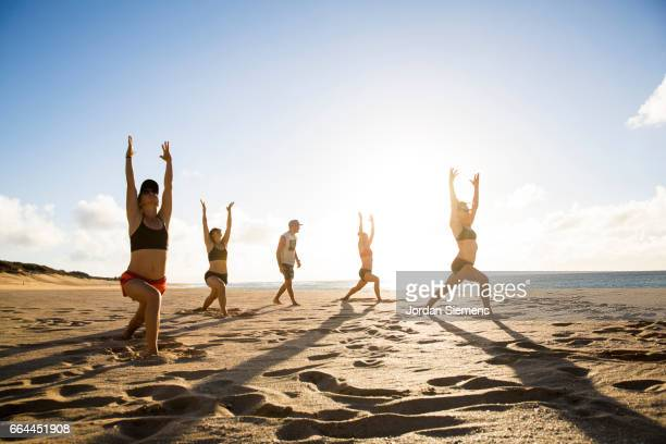 Friends doing yoga in the sand.