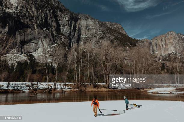 friends dragging kayak across snow, yosemite village, california, united states - peter snow stock pictures, royalty-free photos & images