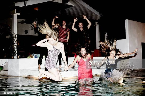 friends dressed up jumping into the pool at night. - pool party stock pictures, royalty-free photos & images