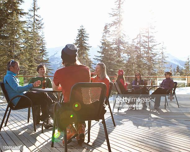 Friends drink beer on ski lodge patio