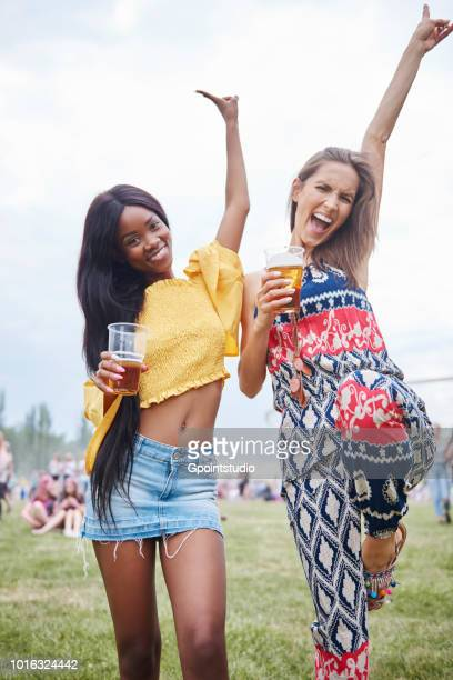 friends drinking and dancing with arms raised in music festival - festival goer stock pictures, royalty-free photos & images