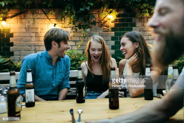 Friends Drinking And Having A Laugh Together Before Eating Dinner