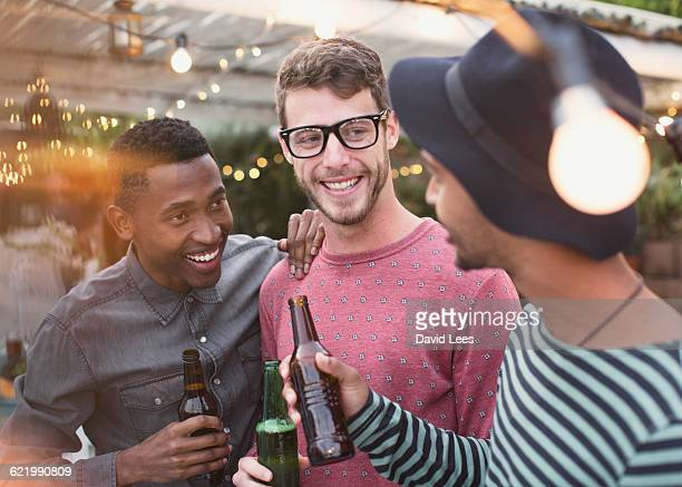 friends drinking and laughing at poolside party - men friends beer outside stock pictures, royalty-free photos & images