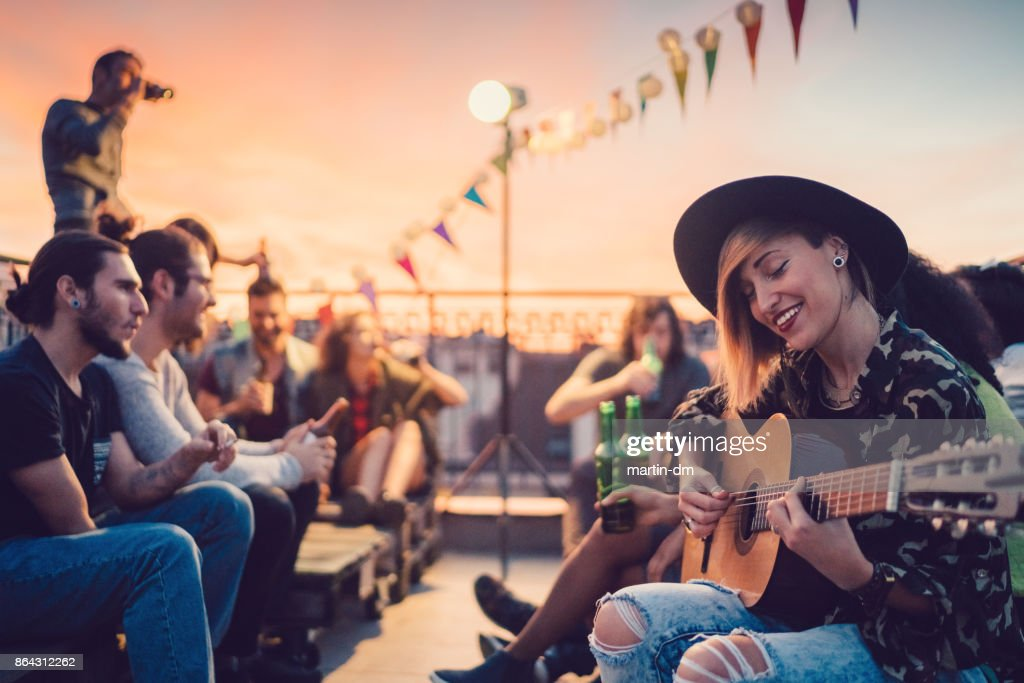 Friends drinking and partying on the rooftop : Stock Photo