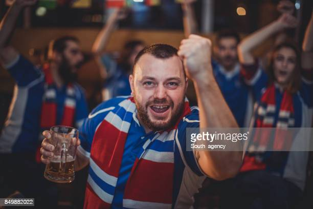 Friends drinking beer and watching game in bar