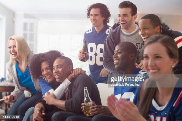 Friends drinking beer and watching game on television