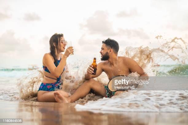 amigos que bebem a cerveja no beira-mar - espuma sintética - fotografias e filmes do acervo