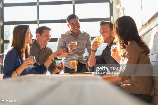 friends drinking beer in brew pub - low angle view stock pictures, royalty-free photos & images