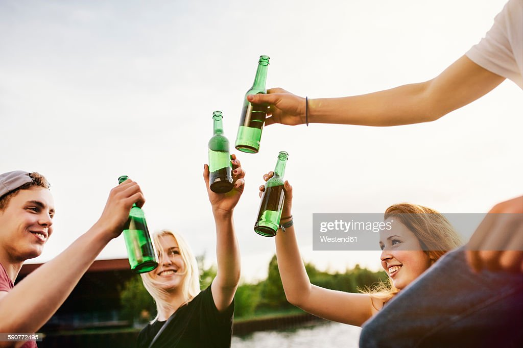 Friends drinking beer together at the waterside : Stock-Foto