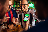 Friends drinking beer, watching soccer game and using mobile app for betting