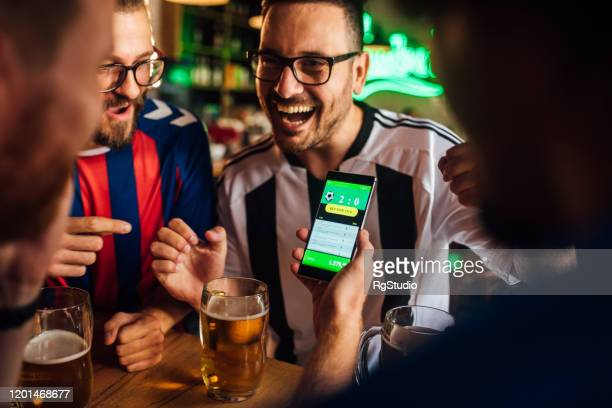 friends drinking beer, watching soccer game and using mobile app for betting - match sport imagens e fotografias de stock