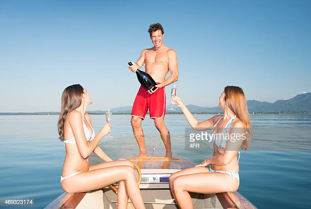 friends drinking champagne on a boat party - crazy holiday models stock photos and pictures
