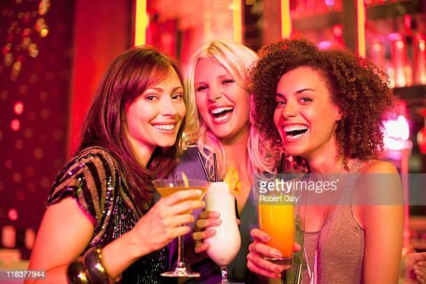 Friends drinking cocktail in nightclub