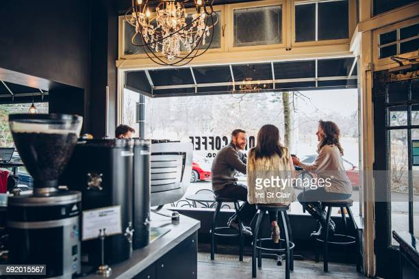 friends drinking coffee in cafe - mid adult stock pictures, royalty-free photos & images