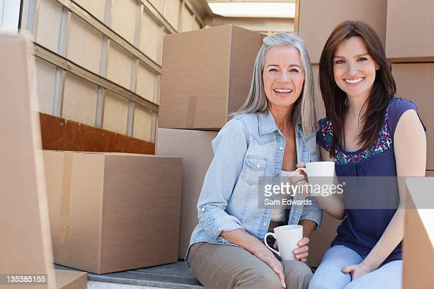 Friends drinking coffee on back of moving van