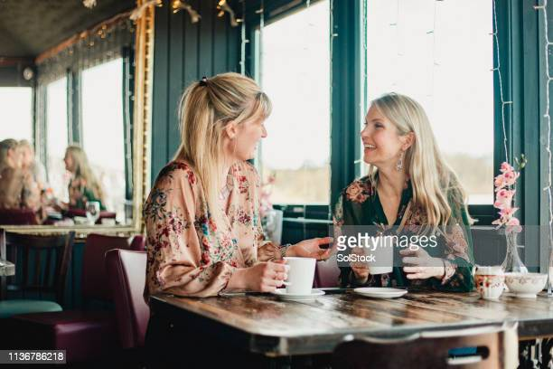 friends drinking coffee - nur frauen stock-fotos und bilder