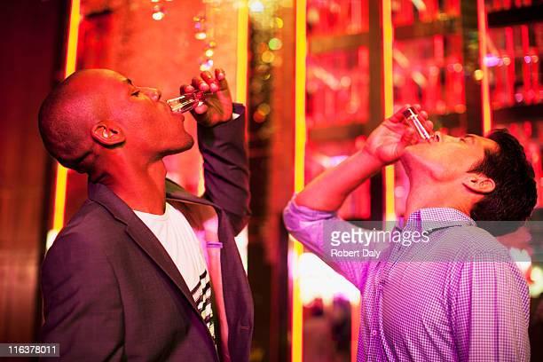 Friends drinking from shot glasses in nightclub