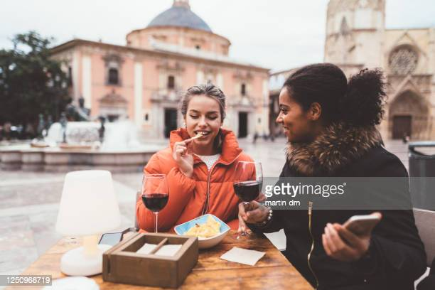 friends drinking red wine in restaurant during travel - valencia spain stock pictures, royalty-free photos & images