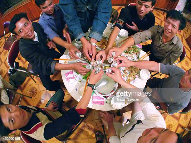 Friends drinking rice alcohol after meal in a small roadside guesthouse hosting only local people . Other keywords: friendship, alcool, drinking,...