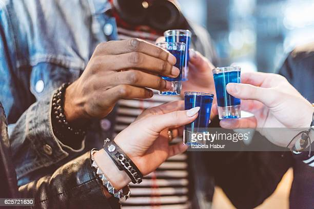 Friends drinking shots, close up of hands