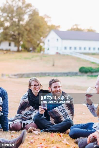 Friends drinking wine in rural field