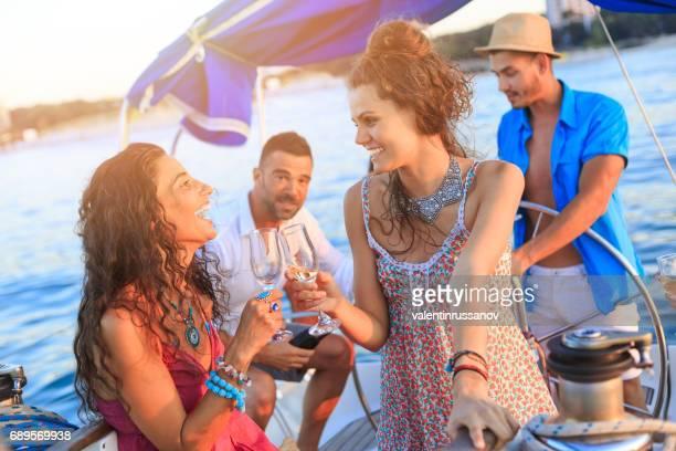 Freunde, trinken Wein auf Yacht bei Sonnenuntergang