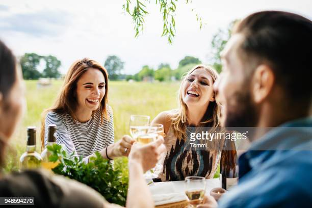 friends drinking wine together having lunch outdoors - farm to table stock photos and pictures
