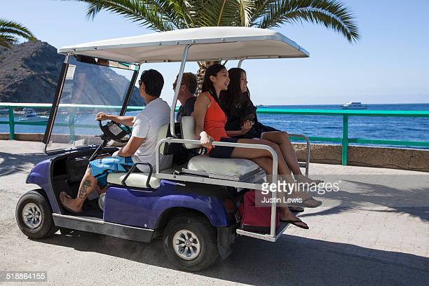 4 friends drive golf cart on harbor jetty - catalina island stock photos and pictures