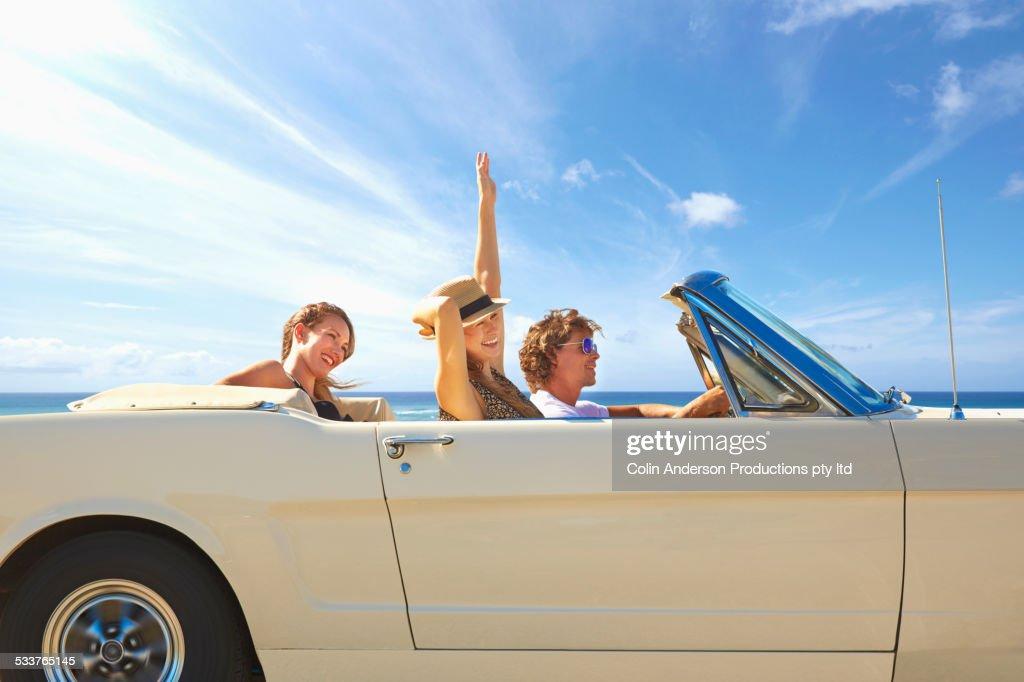 Friends driving convertible under blue sky : Foto stock