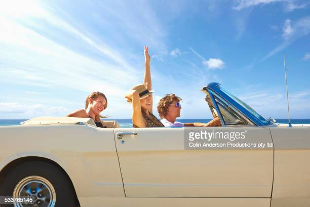 Friends driving convertible under blue sky