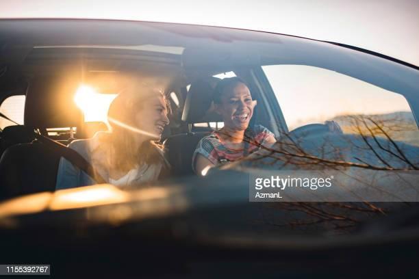 vrienden rijden in een auto op een zonnige dag - landvoertuig stockfoto's en -beelden
