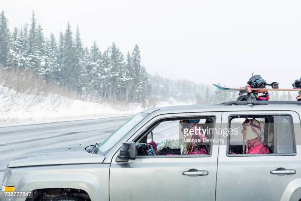 friends driving in car in winter - driving in snow stock photos and pictures