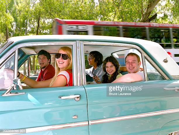 Friends driving in car, smiling, portrait