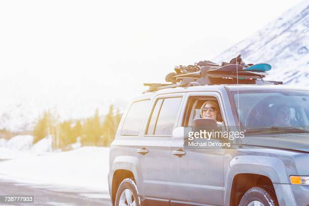 Friends driving in car with snowboards in winter