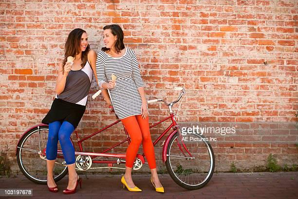 Friends eat ice cream next to tandem bike