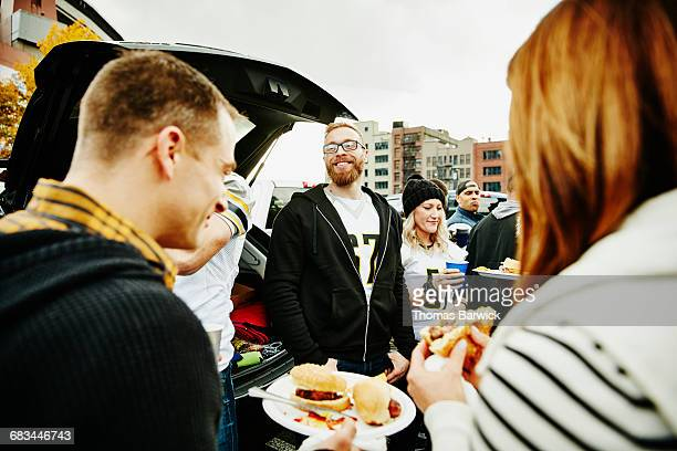 Friends eating and drinking at tailgating party