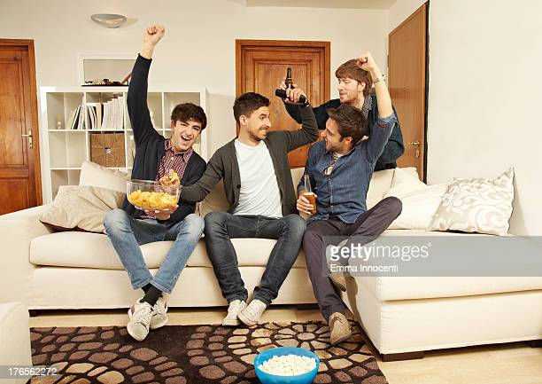 Friends eating and drinking on sofa