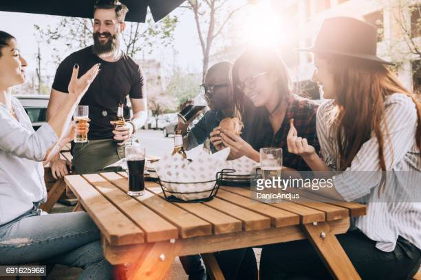 friends eating and drinking outdoors and having fun - solar flare stock pictures, royalty-free photos & images