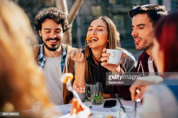 friends eating at a restaurant - restaurant stock photos and pictures